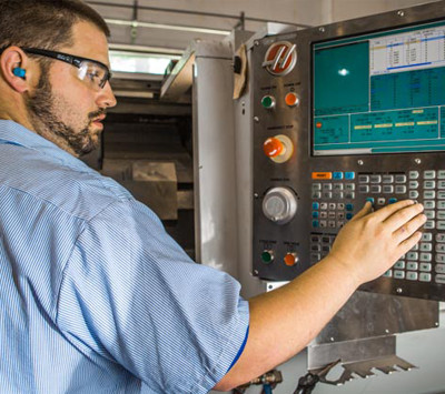 HP Manufacturing employee at the controls of a plastics machining unit at our plant in Cleveland, OH
