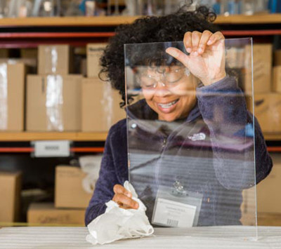 HP Manufacturing employee cleaning a clear plastic acrylic piece